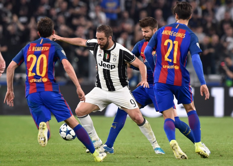 Juventus' Gonzalo Higuain in action with Barcelona's Sergi Roberto, Gerard Pique and Andre Gomes